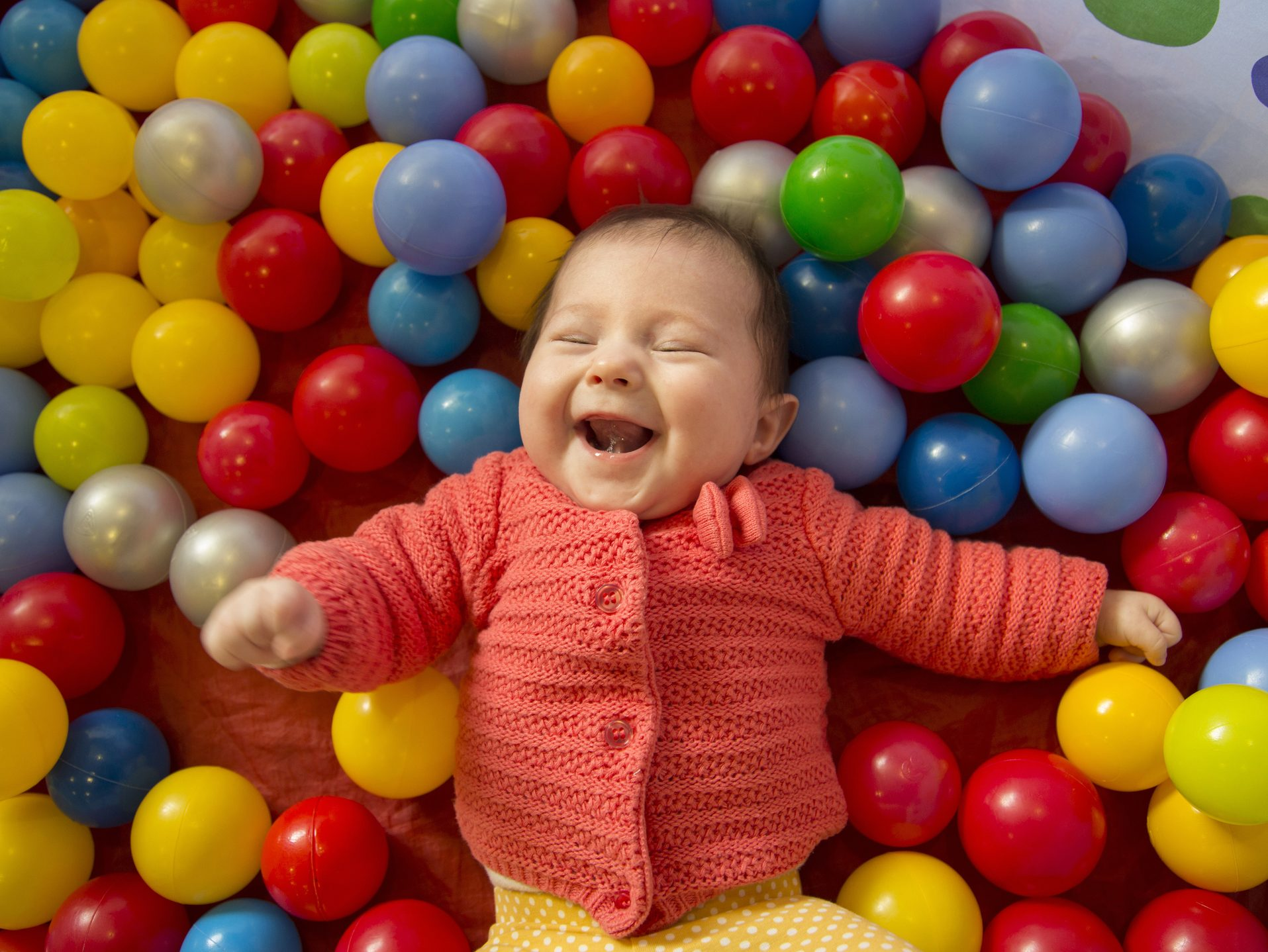 baby girl laughing in a sensory ball pit